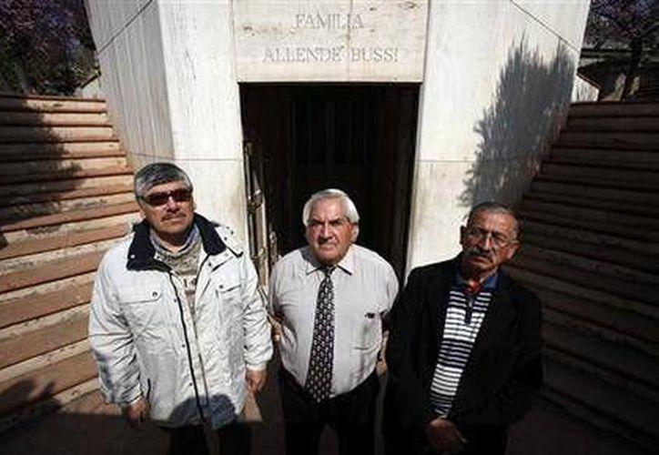 Milton Silva, de 62 años, Pablo Zepeda, 62 años, y Jaime Hernández, 66 años, quienes posan frente al mausoleo donde reposan los restos del presidente socialista Salvador Allende. (Agencias)