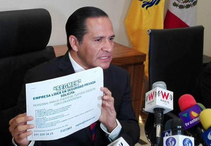 El fiscal General del Estado de Jalisco, Eduardo Almaguer Ramírez, enseñó durante la conferencia de prensa los volantes en donde solicitan a los interesados. (@ealmaguerr)