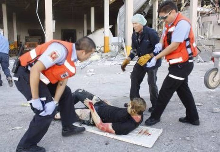 Socorristas ayudan a un hombre que resultó herido en la explosión. (Agencias)