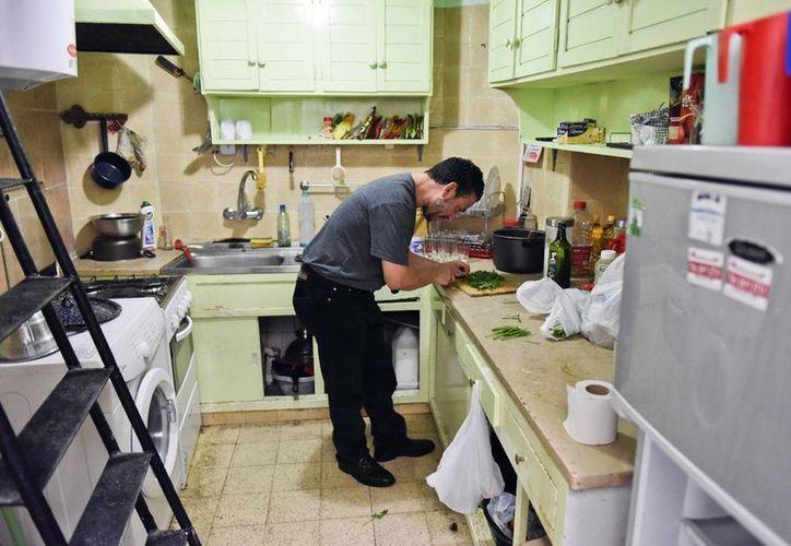 El tunecino Adel bin Muhammad El Ouerghi pica perejil en la casa que comparte con otros cinco exdetenidos de Guantánamo en Montevideo, Uruguay. (Agencia)