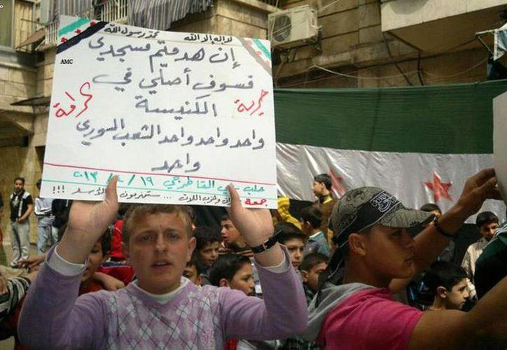 Un ciudadano se manifiesta con una pancarta contra el régimen en Alepo. (Agencias)