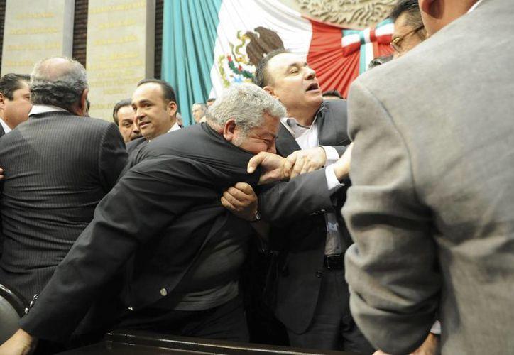 José Rangel Espinosa jalonea a Manuel Huerta Ladrón de Guevara durante la discusión de la discusión del seguro de desempleo en la Cámara de Diputados. (Notimex)