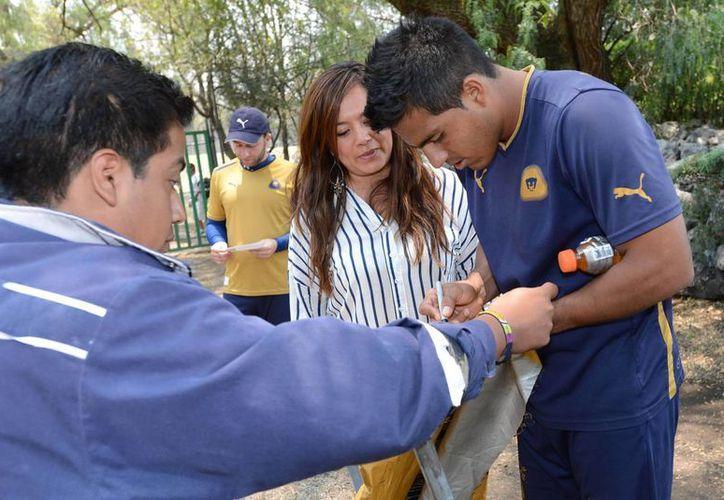 Luego de su entrenamiento de este martes, jugadores de Pumas firmaron autógrafos a sus seguidores. (Notimex)