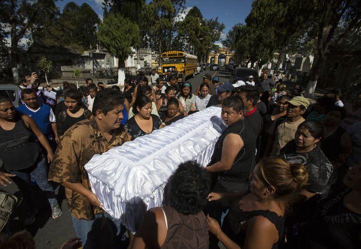 Gente carga el ataúd de Madelyn Patricia Hernández Hernández, una niña de 14 años que murió en el incendio del Hogar Seguro Virgen de la Asunción, en el cementerio de la capital de Guattemala, 10 de marzo de 2017. (AP/Moises Castillo)
