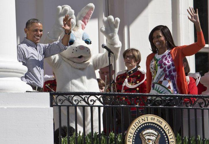 El presidente Barack Obama y la primera dama Michelle Obama con el Conejo de Pascua saludan a las familias que participan en la búsqueda de Huevos de Pascua de la Casa Blanca. (Agencias)