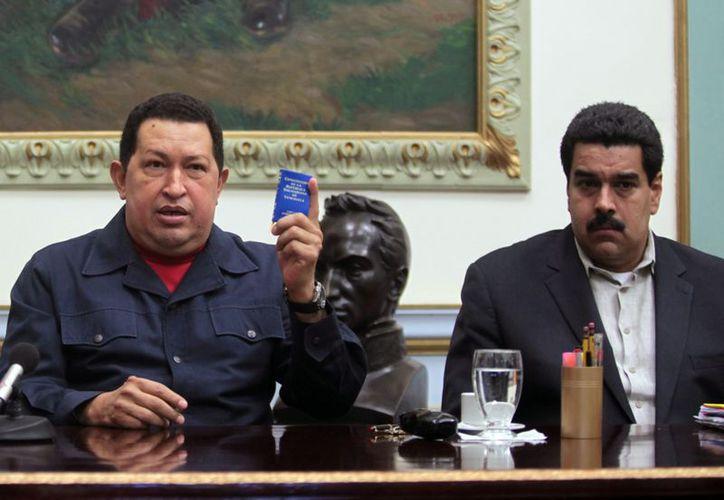 Imagen del 8 de diciembre pasado del presidente Hugo Chávez mostrando una Constitución de Venezuela, acompañado del vicepresidente Nicolás Maduro. (Agencia AP)