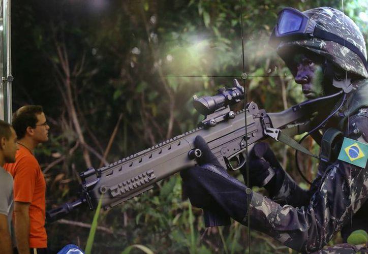 Visitantes observan la imagen de un soldado brasileño, durante la feria internacional de armamento LAAD Defence & Security, en Río de Janeiro. (EFE)
