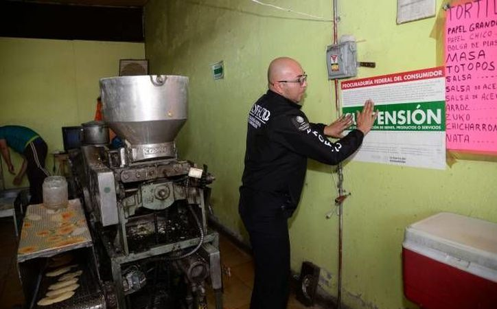 Un funcionario de Profeco coloca sellos de suspensión de actividades a una tortillería, por irregularidades en la venta del producto. (Notimex)