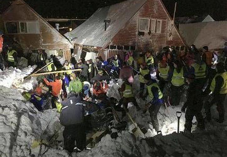 Equipos de búsqueda y rescate trabajan luego que una avalancha destruyó varias casas en Longyearbyen, Noruega. Autoridades reportan un muerto y nueve heridos, también hay desaparecidos. (AP)