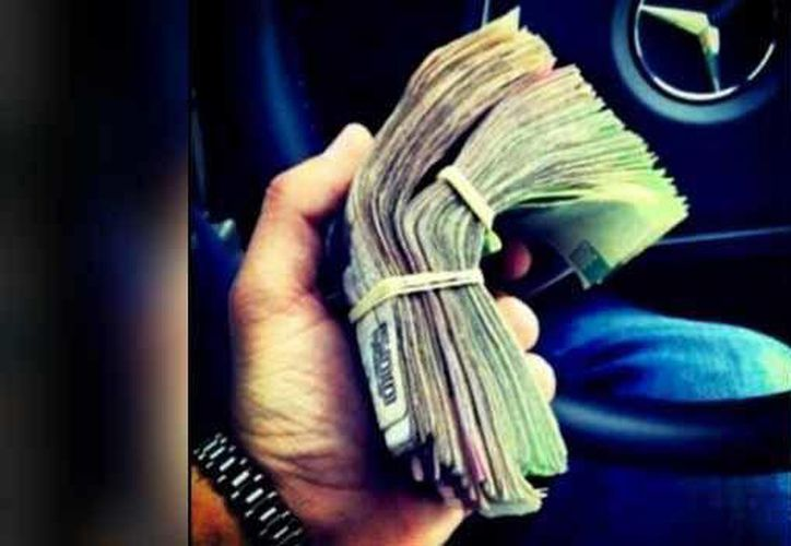 En una de las fotos dan a conocer dinero que sirve 'para la banda'. (Twitter/@AlfredoGuzma)