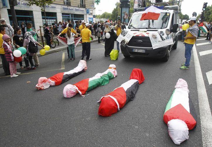 En Francia algunas personas se envolvieron en banderas palestinas como si fuerna cadáveres y se colocaron en la calle, mientras manifestantes pro-palestinos corean consignas anti-israelíes. (Agencias)