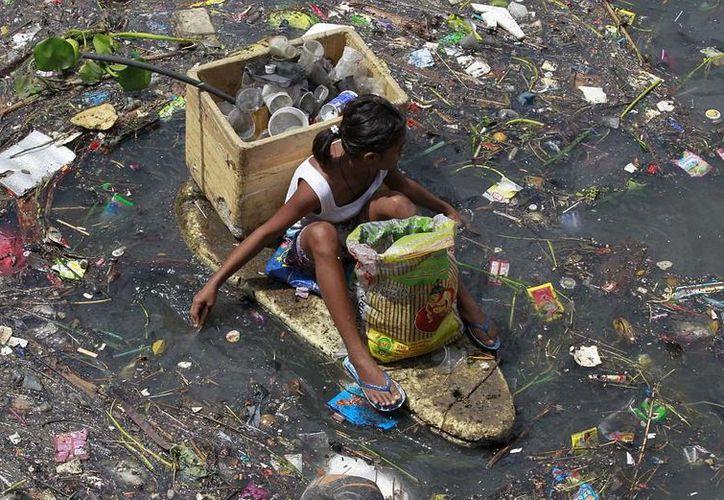 Algunos niños usan pequeñas balsas o barcos improvisados para recoger material reciclable de los ríos. (dailymail.co.uk/Reuters)