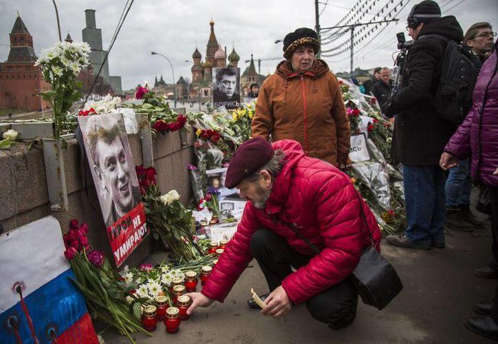 Varias personas visitan el lugar donde fue asesinado Boris Nemtsov, líder opositor y fuerte crítico del presidente ruso Vladimir Putin, en Moscú, Rusia. (Agencias)