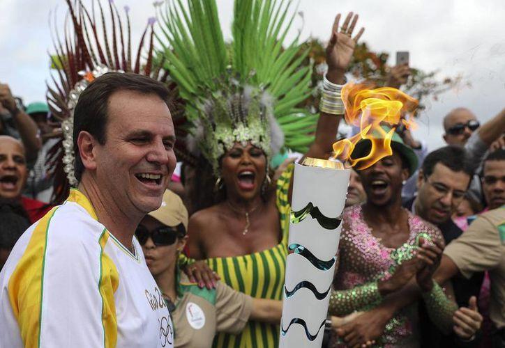 El alcalde de Río de Janeiro, Eduardo Paes (i), recibe la antorcha olímpica a su llegada en la ciudad de Río de Janeiro, Brasil, (EFE)