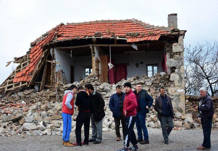 Un grupo de hombres captados frente a una casa destruida por sismos que sacudieron el norte de la costa del Mar Egeo, el lunes 6 de febrero del 2017 en la villa de Yukarikoy, provincia de Canakkale, en Turquía. (Mustafá Suicmez/DHA-Depo Photos vía AP)