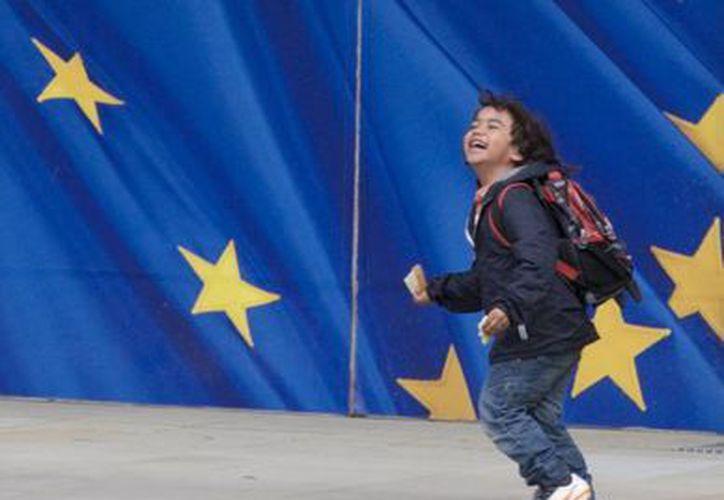 Un niño corre por delante de una puerta con el logo de la Unión Europea impreso sobre ella en la sede de la Unión Europea en Bruselas. (Agencias)