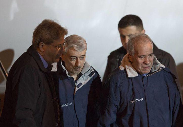 Gino Pollicardo (c) y Filippo Calcagno, al arribar al aeropuerto Campino de Roma, Italia, el 6 de marzo de 2016. (AP/Ricardo De Luca)