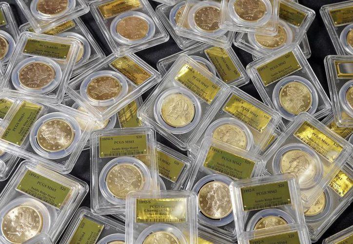 Imagen del pasado 25 de febrero que muestra algunas de las 1,427 monedas de la época de la Fiebre del oro encontradas por una pareja que paseaba a su perro. (Agencias)