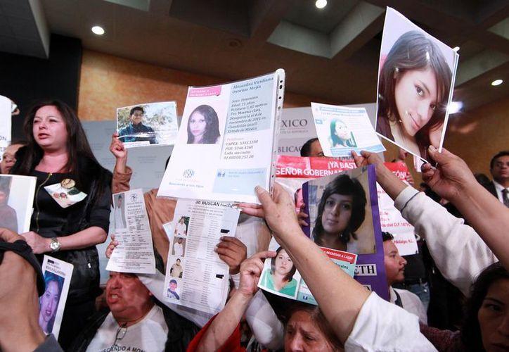 Familiares de víctimas de la violencia mostraron pancartas y fotos de sus seres queridos en la presentación de la ley General de Víctimas, el miércoles en Los Pinos. (Notimex)