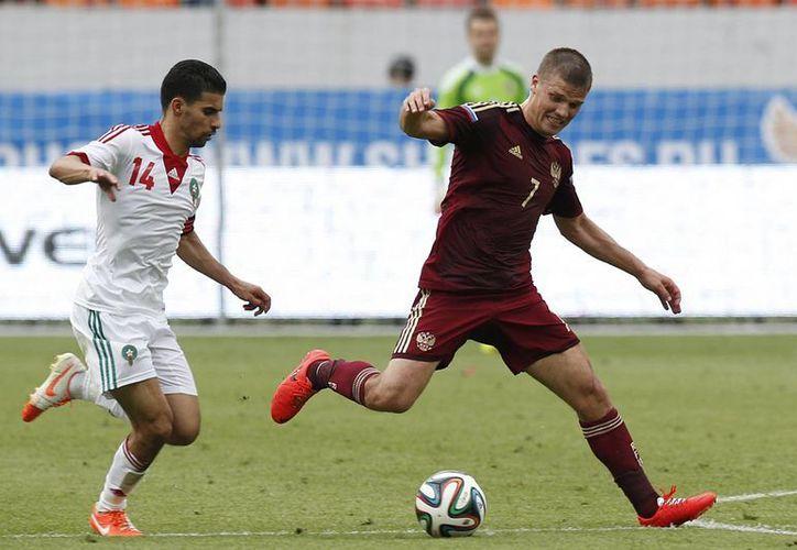 El ruso Igor Denisov (d) disputa el balón con el marroquí Mbark Boussoufa en el más reciente partido amistoso de Rusia, que no podrá contar con su capitán para el Mundial. (Foto: AP)