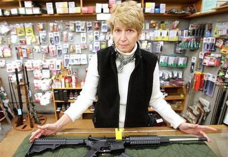 La dueña de la tienda Superior Shooters Supply, Pat Kukull, posa con un fusil DPMS Oracle apartado por un cliente, el 20 de diciembre de 2012. (Agencias)