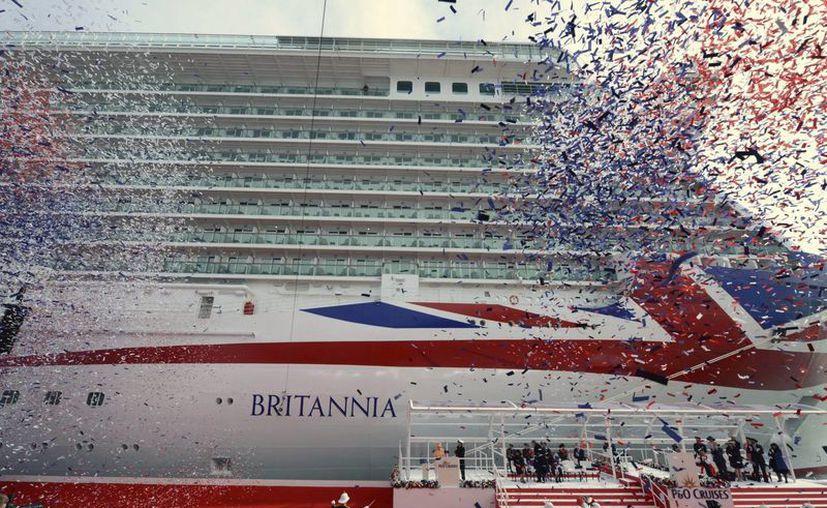 """Fotografía facilitada por la empresa de cruceros P&O que muestra a la reina Isabel II de Inglaterra y al príncipe Felipe, duque de Edimburgo, (c-al fondo) durante una ceremonia en la que han bautizado con el nombre de """"Britannia"""" al buque insignia de la compañía naviera, en el puerto de Southampton, Reino Unido. (EFE)"""