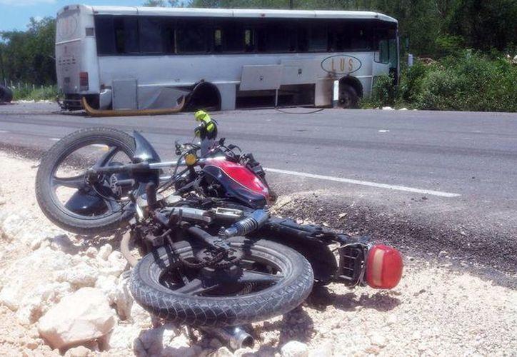La motocicleta quedó a un lado de la carretera Mérida-Oxcutzcab. Al autobús se le salió el eje con todo y llantas. (José Acosta/SIPSE)