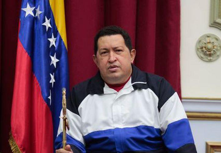 Chávez sostiene la bandera de Venezuela durante una reunión con su gabinete. (Agencias)