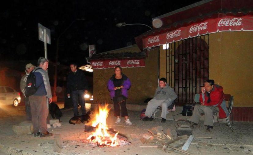 Un grupo de personas espera el amanecer junto a una hoguera, después de que un fuerte temblor afectara la región del Maule en la ciudad chilena de Talca, el pasado mes de marzo. (EFE/Archivo)