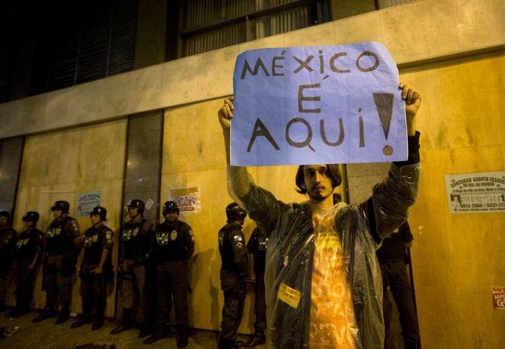 """Un hombre sostiene un cartel que dice en portugués """"México está aquí"""". (Agencias)"""