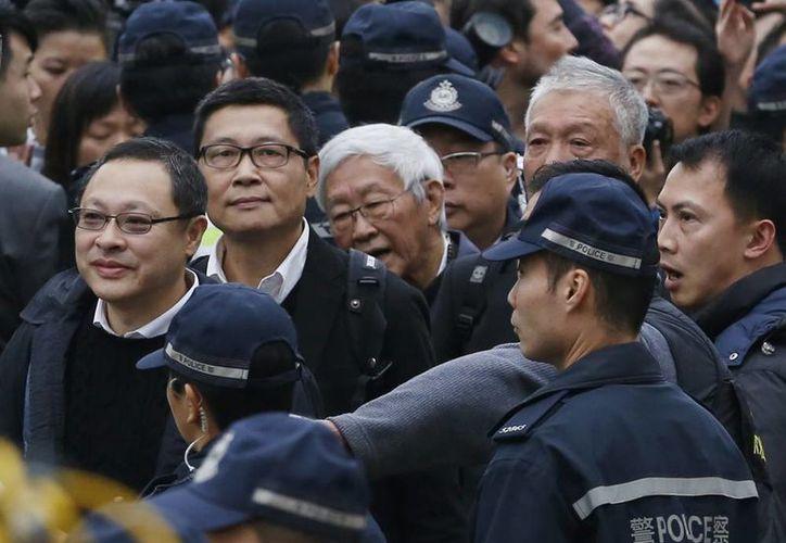 Cuatro líderes de las protestas (de izquierda a derecha) Benny Tai Yiu-ting, Chan Kin-man, Joseph Zen y Chu Yiu-ming, rodeados por la policía, caminan hacia una comisaría en Hong Kong para entregarse y asumir la responsabilidad por las protestas prodemocracia. (Agencias)