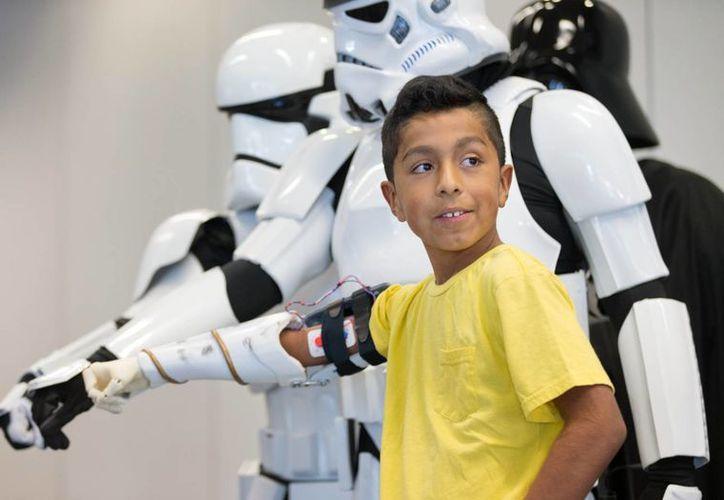 Alvin García Flores con personajes de la Guerra de las Galaxias (Star Wars) muestra el brazo artificial que le obsequiaron, en Omaha, Nebraska, EU. (Foto: Matt Miller/The World-Herald via AP)
