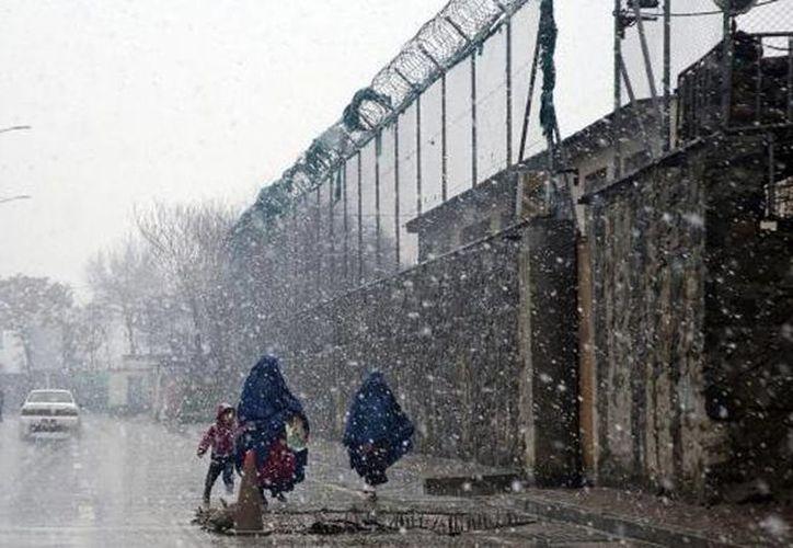 Mujeres afganas cubiertas con burkas caminan en Afganistán en medio de una tormenta de nieve. (Agencias)