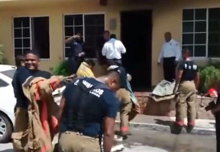 Imagen de los bomberos en el momento que tuvieron que despojarse de sus equipos para demostrar que no se robaron nada del hotel The Mexican Inn en Los Cabos. (Captura de pantalla de YouTube)
