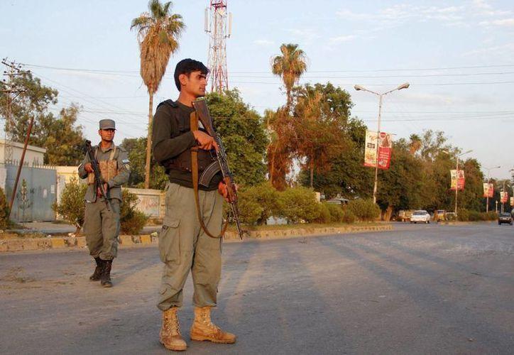 Policías afganos inspeccionan el lugar de un atentado con bomba registrado al paso de unos vehículos en Jalalabad, Afganistán. (EFE/Archivo)