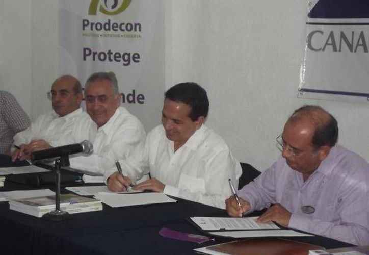 El presidente de la Canaco local, Manuel López Campos, y el delegado regional de la Prodecon, Emiliano Oliva, firman el convenio. (Cortesía)