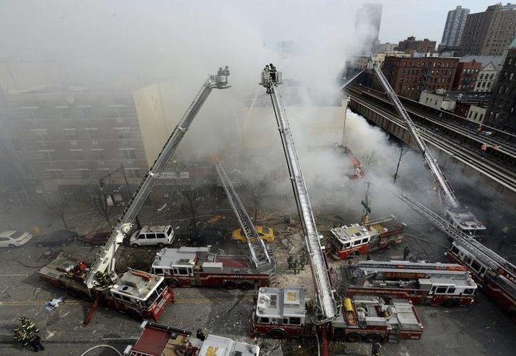 Varios bomberos trabajan en la extinción de un incendio declarado en un edificio del barrio de Harlem, Nueva York. (EFE)