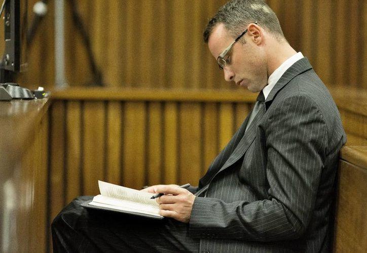 Pistorius lee durante una de las sesiones del juicio que se celebra contra él en el Tribunal Superior de North Gauteng en Pretoria, Sudáfrica. (EFE)