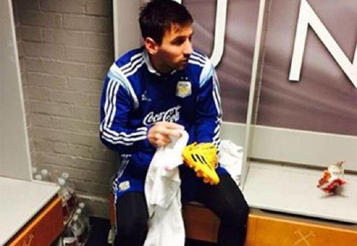 Foto publicada por Lionel Messi, en la red social Facebook. ¡Poniéndolos a punto!, reza la frase que acompaña la imagen en donde se le ve mientras parece limpiar sus botines. (excelsior.com.mx)
