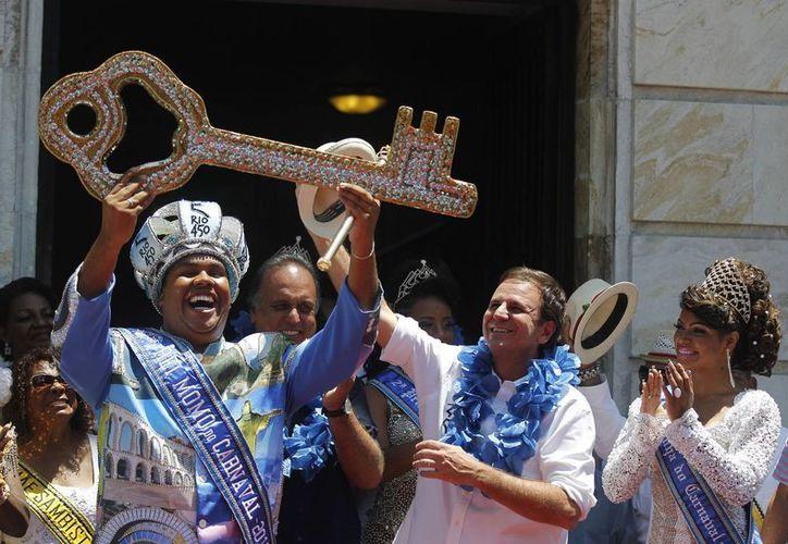 El rey Momo, Wilson Dias da Costa Neto (i) recibe la llave de Río de Janeiro del alcalde Eduardo Paes (c). Junto a ellos el gobernador Luiz Fernando Pezao y la reina Clara Paixao. (Fotos: AP)