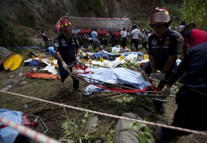 Bomberos y socorristas fueron registrados durante las labores de rescate en la zona del accidente. (EFE)