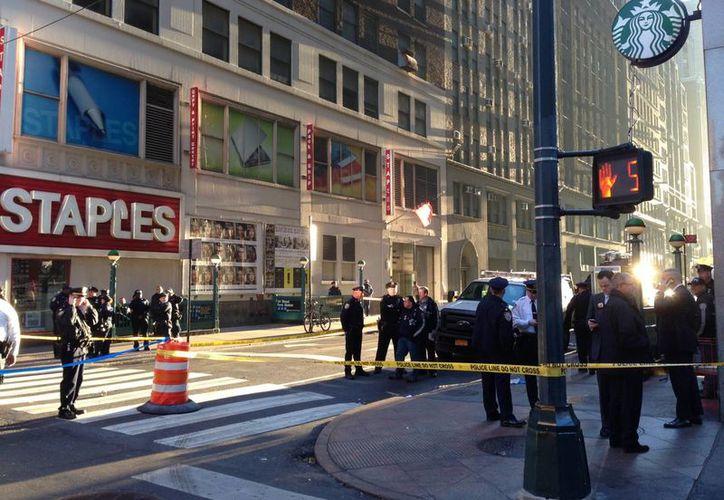Uniformados del Departamento de Policía de Nueva York investigan la zona donde ocurrió un tiroteo en la esquila de las calles 35th Street y Eighth Avenue, en Manhattan. (Agencias)