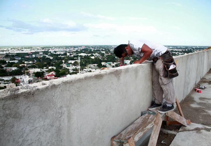 Los trabajadores de la construcción requieren tener seguridad social o seguro popular. Imagen de un empleado mientras labora en el techo de un edificio. (Milenio Novedades)