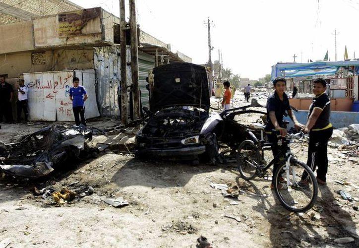 Varias personas observan un vehículo destrozado en el lugar donde se ha producido una explosión en Husainiya, Irak. (EFE)