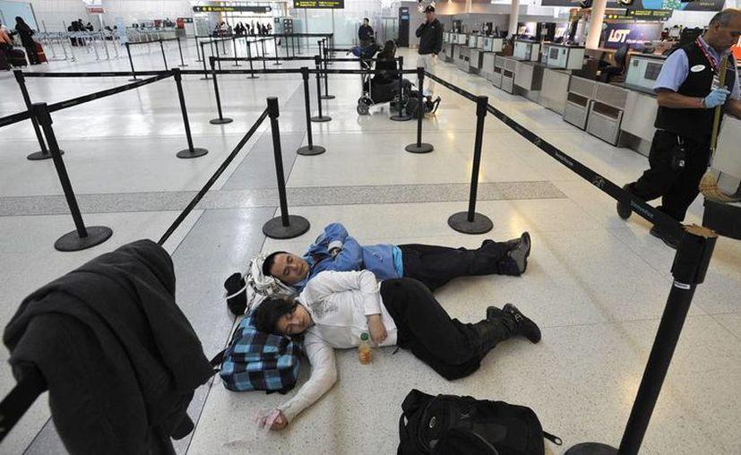 El Gobierno de Estados Unidos informó que al menos 9 personas han muerto a causa del intenso frío provocado por una tormenta invernal. En la imagen, pasajeros descansan en el piso de un aeropuerto de Canadá, por la cancelación de vuelos, a causa del clima. (Agencias)