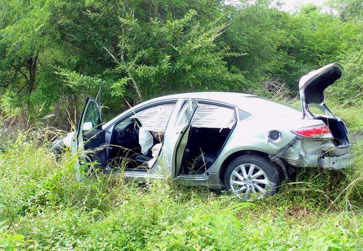 Después del choque contra una vieja camioneta, el Mazda3 de la catedrática quedó desbaratado a un lado de la carretera Hunucmá-Sisal. (Milenio Novedades)