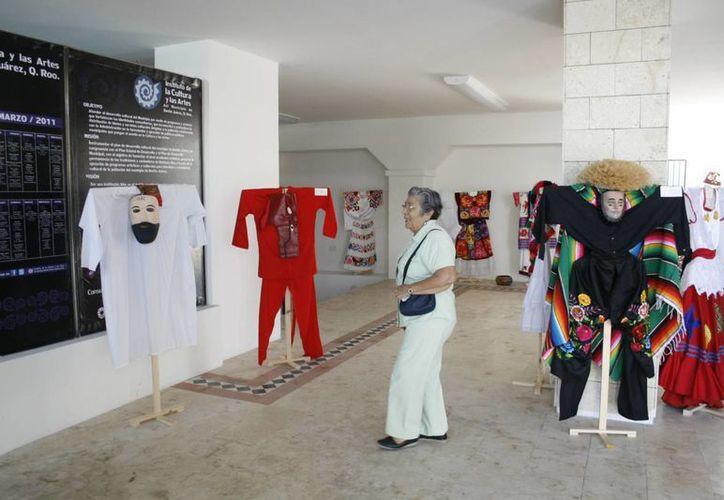 Trajes típicos y obras de arte es lo que se observa en la exposición. (Israel Leal/SIPSE)