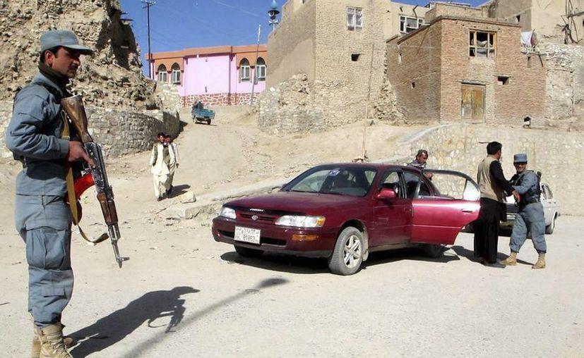 Policías afganos inspeccionan un vehículo en la provincia de Ghanzi, en Afganistán. (Archivo/EFE)