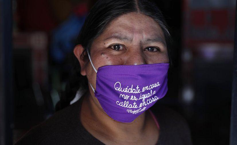 Mujeres feministas bolivianas venden cubrebocas con mensaje para sobrevivir a la crisis económica. (Foto: AP).