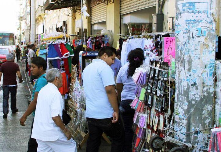 Las calles del centro están llenas de 'obstáculos comerciales'. Imagen de una de las banquetas llenas de gente en el Centro Histórico de Mérida. (Milenio Novedades)